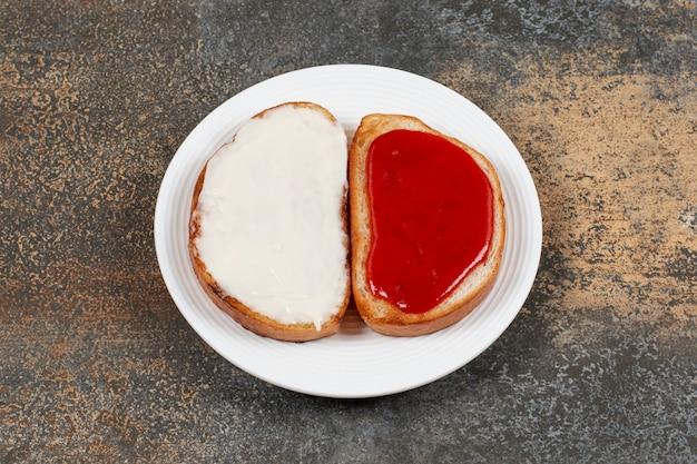 Toast con marmellata di fragole e panna acida sul piatto bianco.