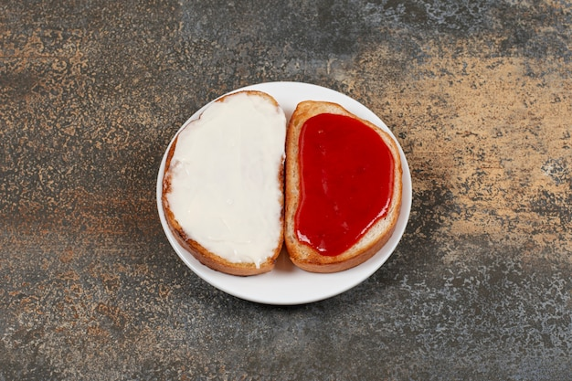 Toasts with strawberry jam and sour cream on white plate.