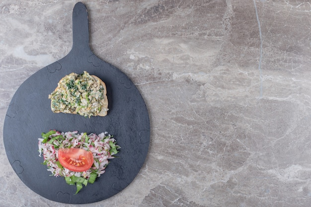 Тосты с вкусным салатом на темной доске.