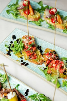 Toasts with tomatoes arugula and grated cheese