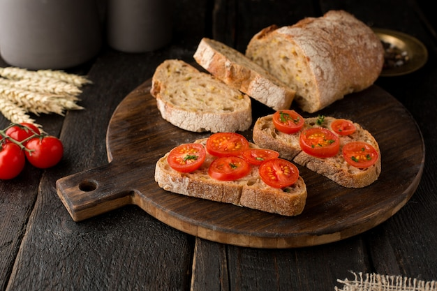 Toasts with tomatoes and bread on a board on wood