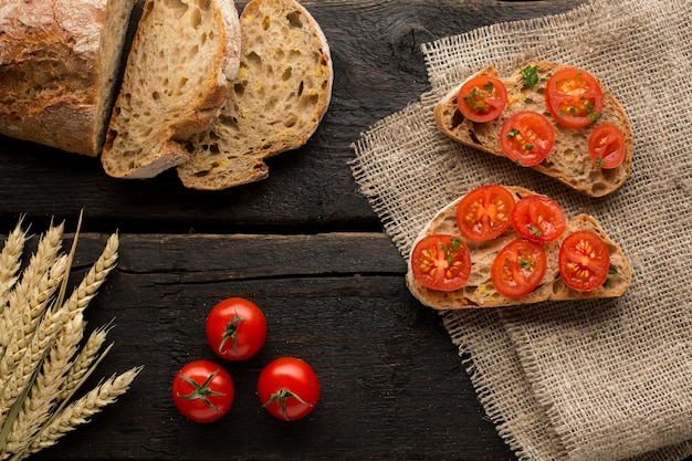 Toasts with tomatoes and bread on a board
