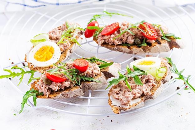 Тосты с тунцом. итальянские бутерброды брускетта с консервированным тунцом, помидорами и каперсами. копировать пространство Premium Фотографии
