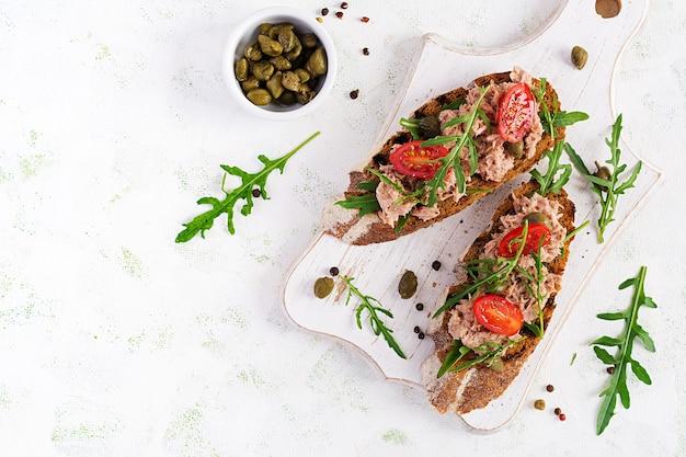Тосты с тунцом. итальянские бутерброды брускетта с консервированным тунцом, помидорами и каперсами. вид сверху, плоская планировка, копия пространства