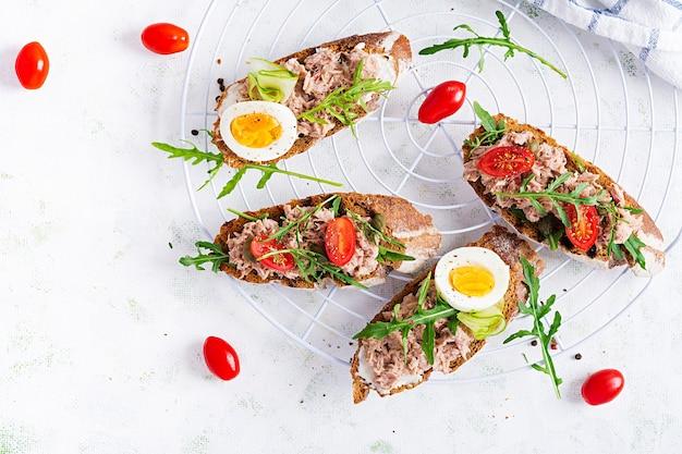 참치 토스트. 통조림 참치, 토마토 및 케이 퍼를 곁들인 이탈리아 브루스케타 샌드위치. 평면도, 평면 위치, 복사 공간