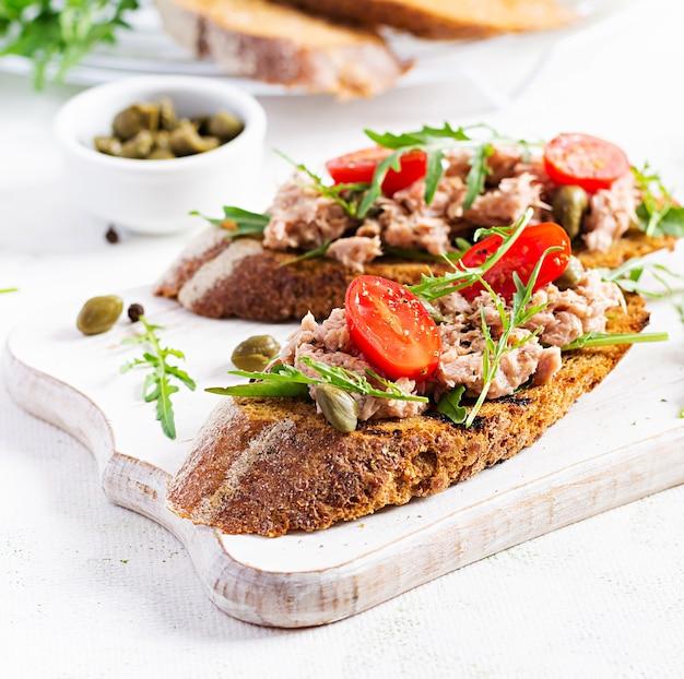 Тосты с тунцом. итальянские бутерброды брускетта с консервированным тунцом, помидорами и каперсами.