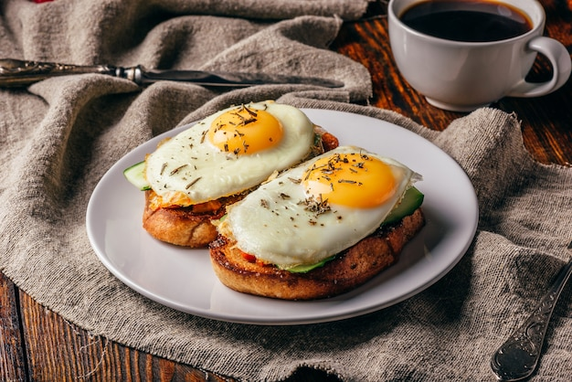 Toasts with vegetables and fried eggs on white plate and cup of coffee over grey rough cloth.