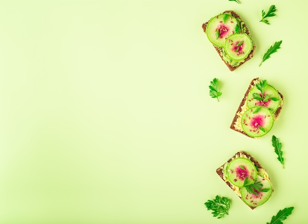 Toasts with watemelon radish avocado and flex seeds on color background top view flat lay design