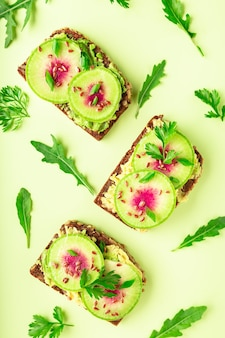 Toasts with watemelon radish avocado and flex seeds on color background top view