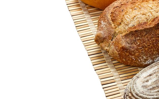 Поджаренный органический хлеб французского хлеба на деревянной доске изолированной на белизне.
