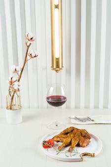 적포도주 한 잔이 든 담배 치킨, 면화 잔가지가 달린 꽃병, 세련된 램프