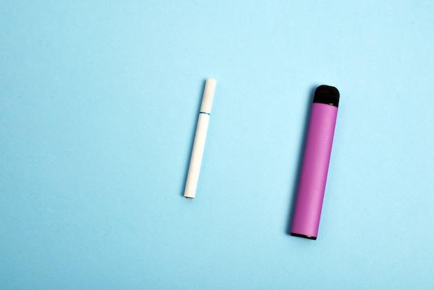 青い背景の上のタバコのタバコと使い捨て電子タバコ選択の概念