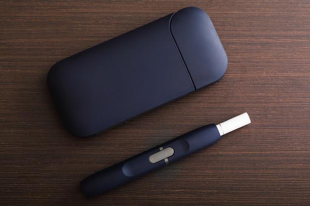 木製テーブルのタバコ加熱システム。伝統的なタバコの代替品