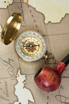 Tobacco pipe and a compass on the map