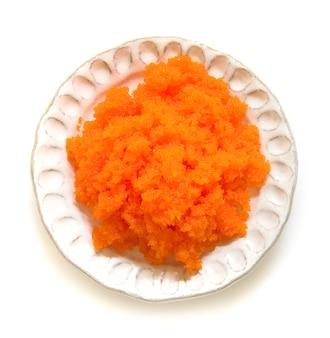 Tobiko egg is orange (flying fish roe) on white plate.