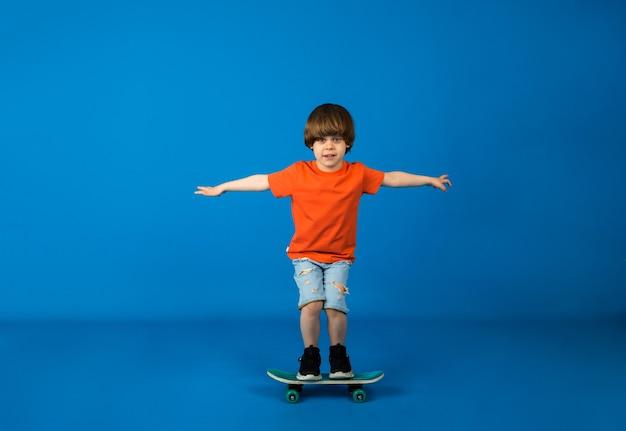 Tシャツとショートパンツを着た男の子の幼児がテキスト用のスペースのある青い表面でスケートボードに乗る