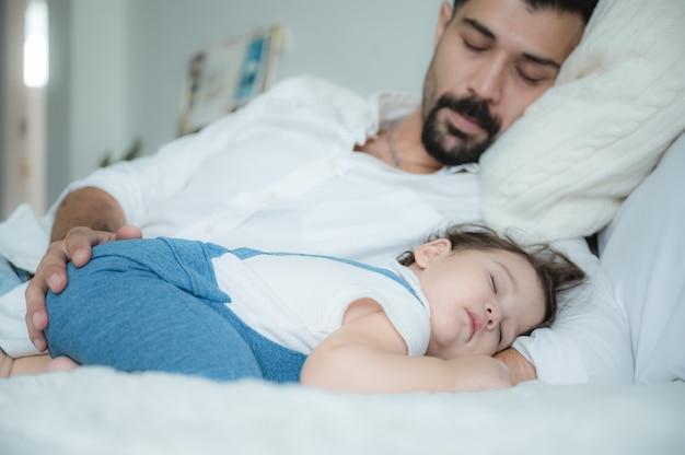 ベッドで寝ている幼児と父親