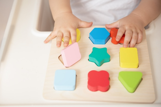 幼児は、おもちゃを色と幾何学的形状で並べ替えます。教育と開発の木のおもちゃ。モンテッソーリゲーム