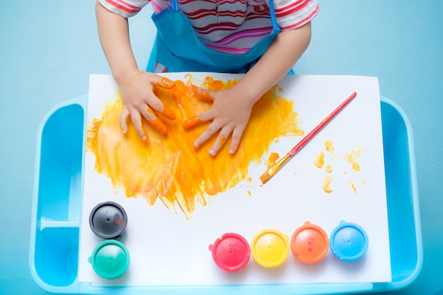Toddler baby boy child finger painting with hands and watercolors