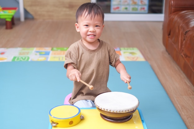 Toddler baby boy child hold sticks & plays a musical instrument drum in play room at home