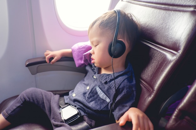 Toddler baby boy child sleeping with safety belt on wearing headphones while traveling in airplane