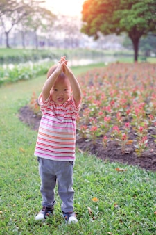 Toddler baby boy child try to practices yoga in tree pose at the park