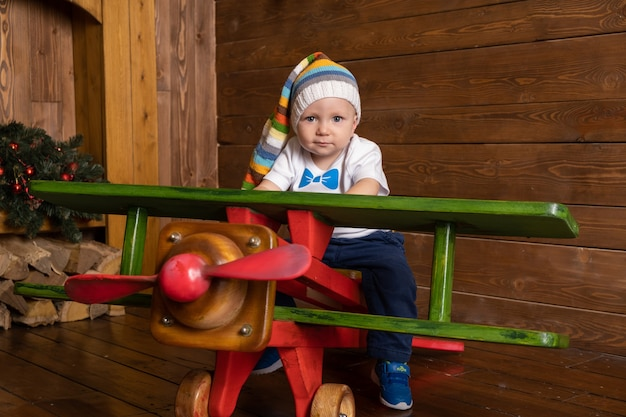 Toddler baby boy is playing in a large wooden plane.