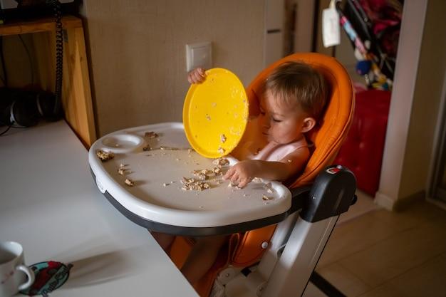 Маленький ребенок ест грязно в стульчике для кормления дома
