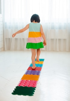 Toddler on baby foot massage mat. exercises for legs on orthopedic massage carpet. prevention of flat feet and hallux valgus