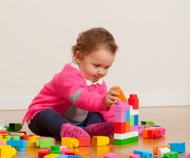 Toddler baby girl playing with rubber building blocks.