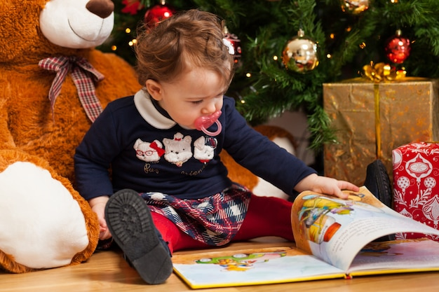 Toddler baby girl reading fairy tales near christmas tree.
