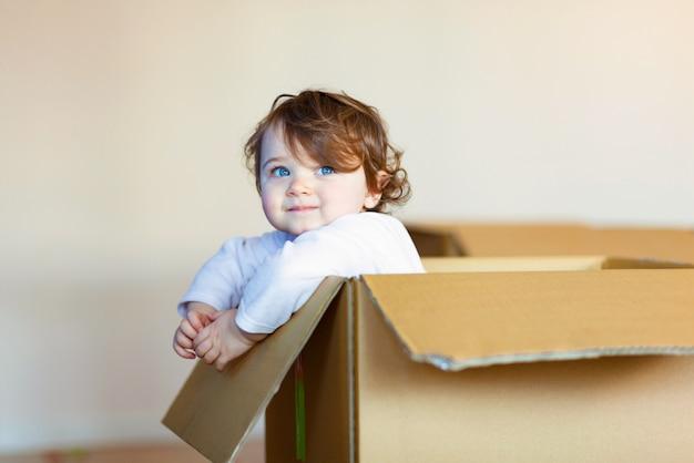 Toddler baby girl sitting inside brown cardboard box.