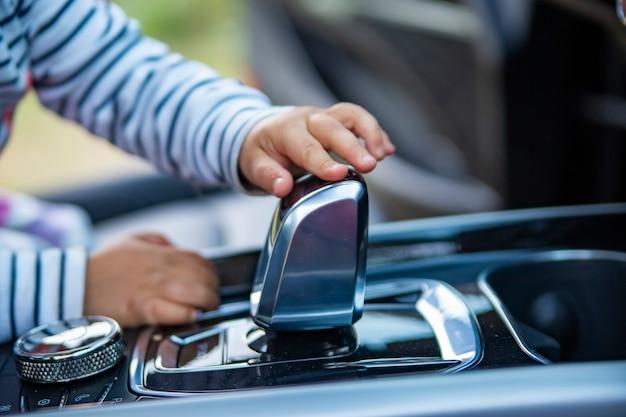 Малыш играет в современном интерьере автомобиля premiun маленький ребенок трогает ручку переключения передач современного автомобиля