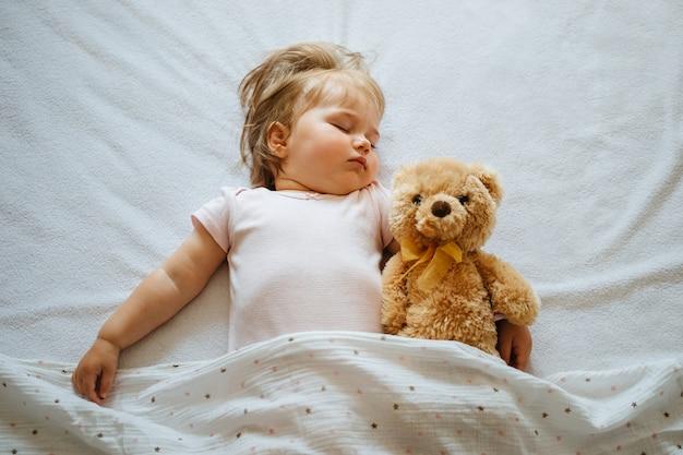 テディベアを抱いて白いシーツで寝ている幼児の赤ちゃん。子供の昼寝時間または就寝時間。上面図。
