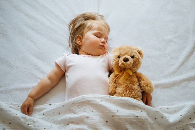 Toddler baby sleeping on white sheets hugging teddy bear. children's nap time or bedtime. top view.