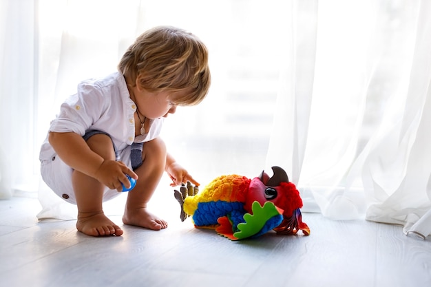 A toddler blonde boy is sitting on the floor at home and playing with bright colorful parrot toy copy space