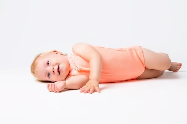 Малышка блондинка смеется в оранжевом боди, сидя на белой стене