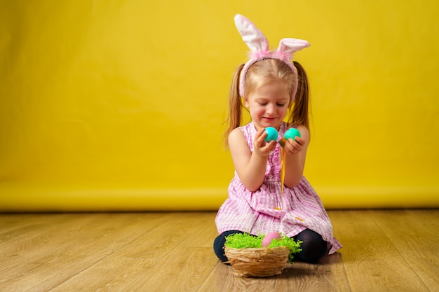 Toddler blonde happy  girl with bunny ears and basket of eggs for easter