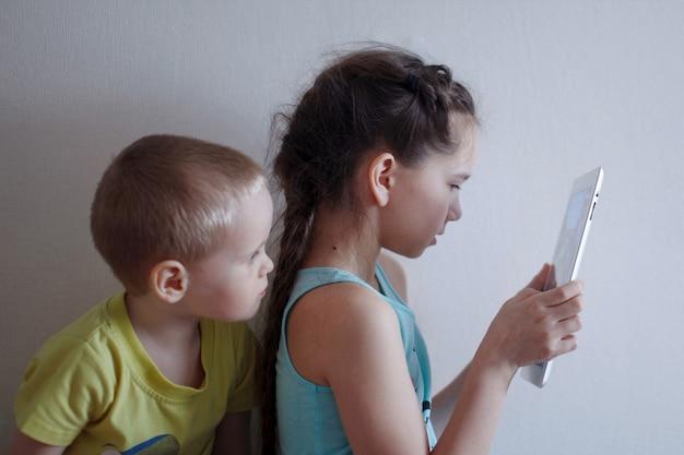 長い三つ編みの幼児の男の子と女の子がスマートフォンを見る