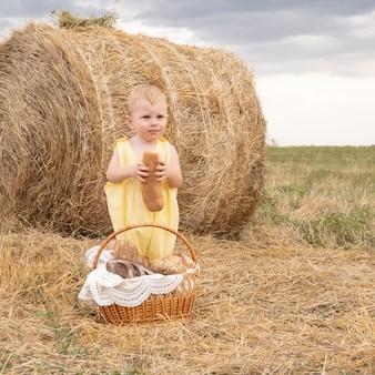 Малыш мальчик блондинка с корзиной хлеба в поле ест багет