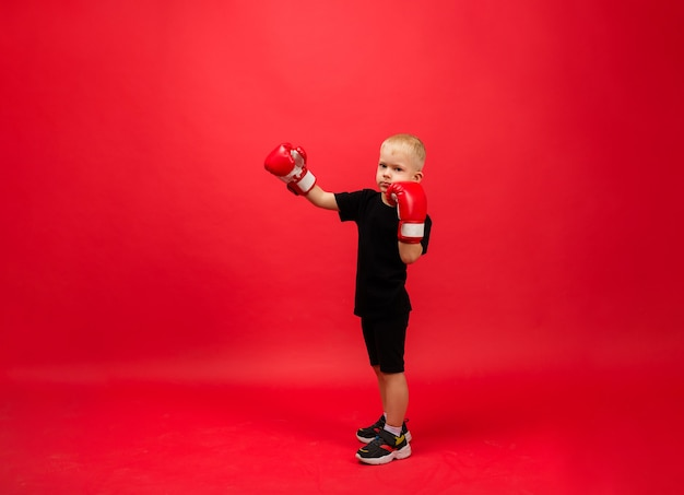 Toddler boy boxer in red boxing gloves stands sideways at full height and makes a punch on a red wall