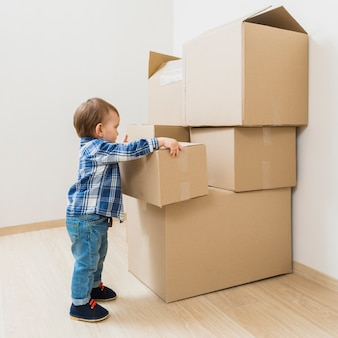 Toddler boy carrying moving cardboard box at new home