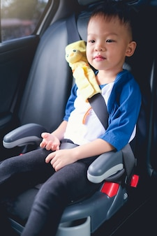 Toddler boy child sitting in booster car seat