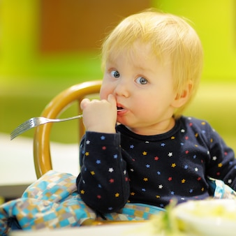 Toddler boy eating food at the indoors cafe