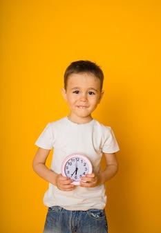 유아 소년은 텍스트를위한 공간이있는 노란색 표면에 알람 시계를 보유하고 있습니다.