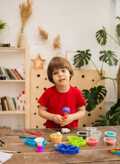 赤いtシャツを着た幼児の男の子は、部屋の木製のテーブルで粘土と形で遊んでいます。細かい運動技能の発達。