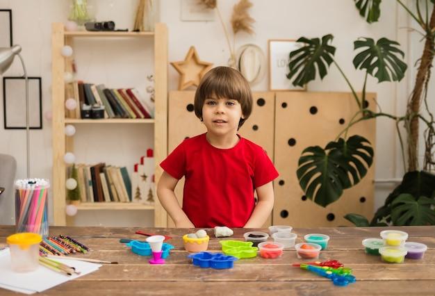 빨간 티셔츠를 입은 유아 소년은 창의적인 용품이 담긴 테이블에 앉아 방 앞을 봅니다.