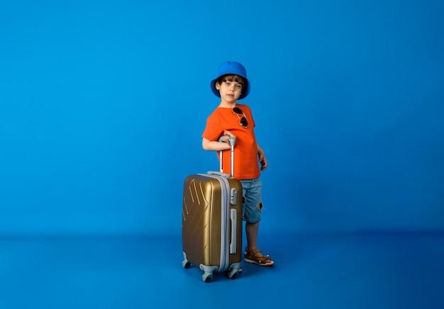 オレンジ色のtシャツとデニムのショートパンツとパナマ帽をかぶった幼児の男の子は、テキスト用のスペースがある青い表面にスーツケースを持って立っています