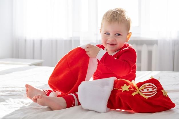 自宅の白いベッドに座っているクリスマスの靴下と赤いスーツを着た幼児の男の子。晴れた朝。