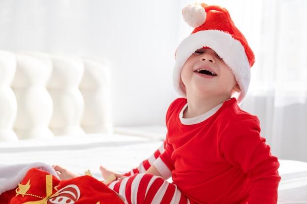 サンタの帽子をかぶった幼児の男の子、自宅の白いベッドに座っているクリスマスの靴下と赤いスーツ。晴れた朝。